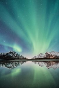 Yellow green aurora lights over mountains and a calm body of water with many stars at night