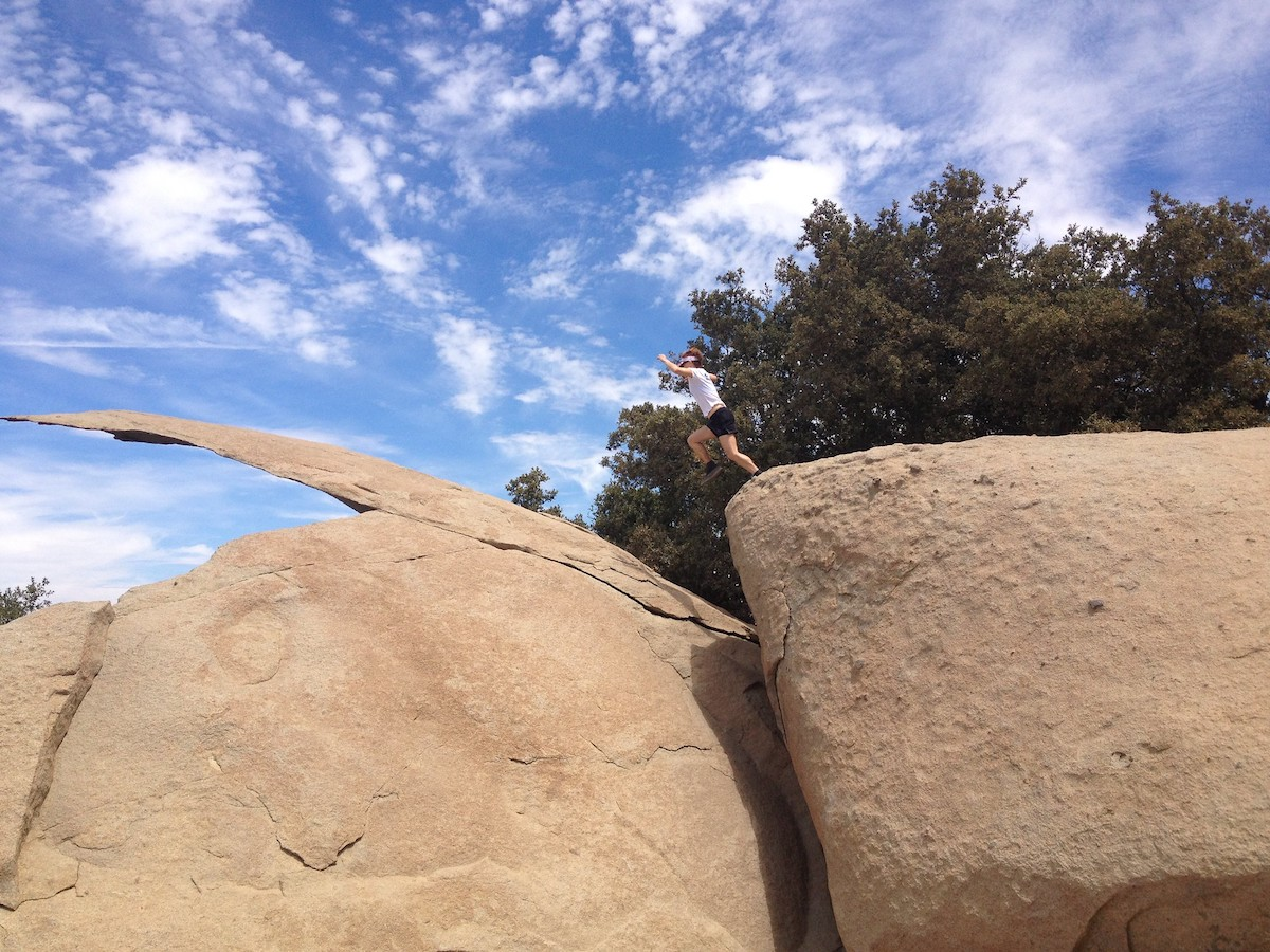 Hiker leaping to the Potato Chip Rock