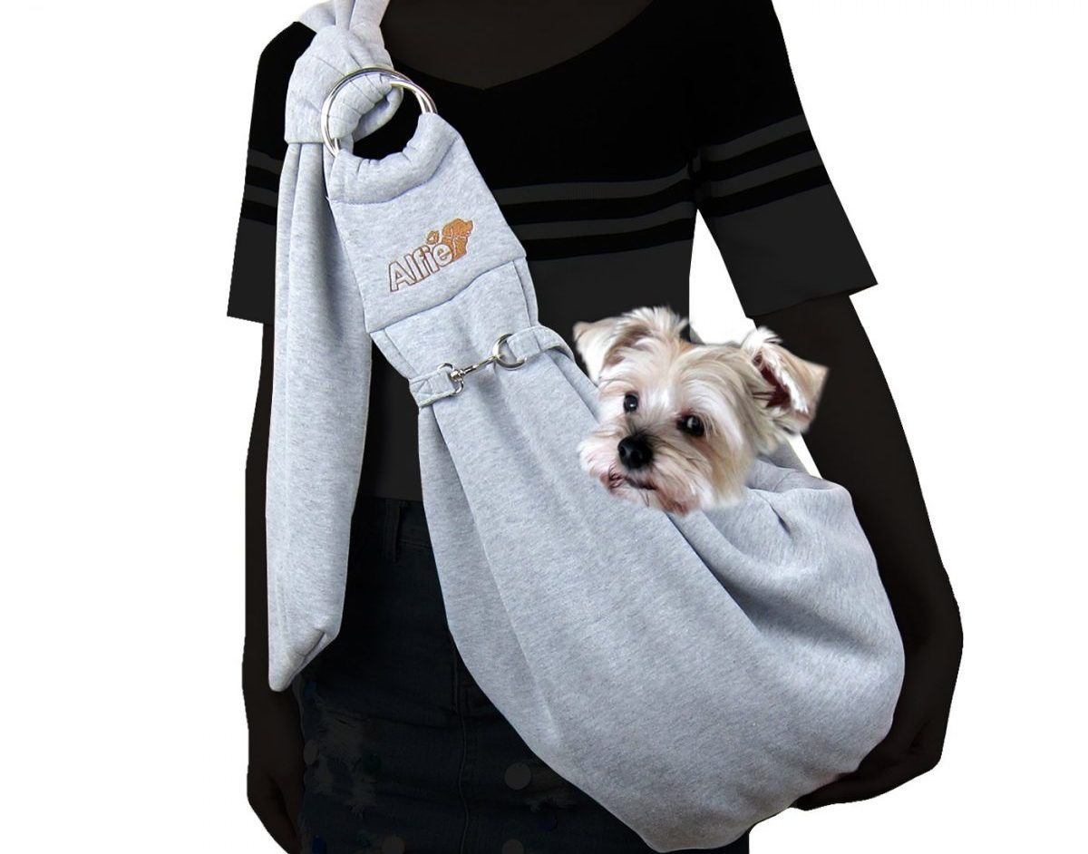A grey Alfie Pet sling bag carrying a small terrier with its head peeking out