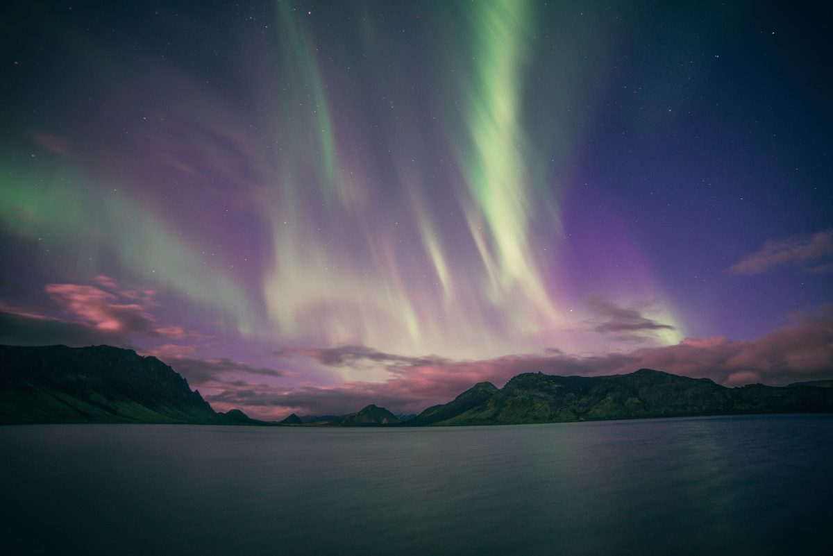 Photo of yellow green and purple aurora lights over a calm body of water with mountains and clouds in the distance in Iceland