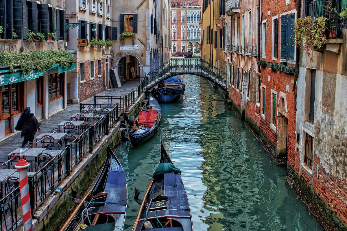 A small street in Venice with a canal and boats and a bridge