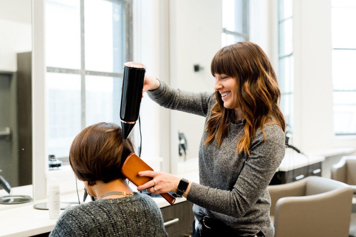 Hairdresser drying women's hair in a Salon in Spain