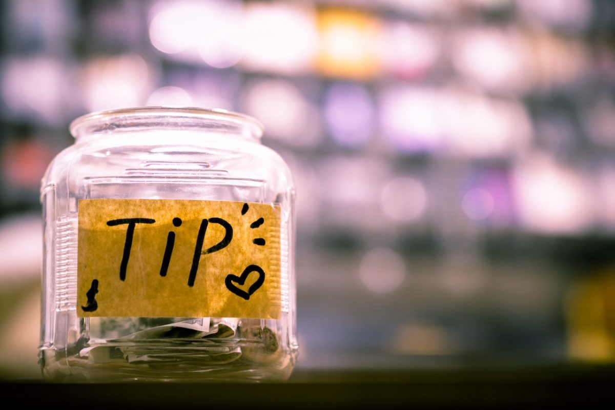 Tipping jar with coins and bank notes