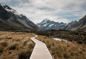 A walkway stretches across grasslands with a mountain range seen at a distance in the Hooker Valley Track, Mount Cook National Park, New Zealand