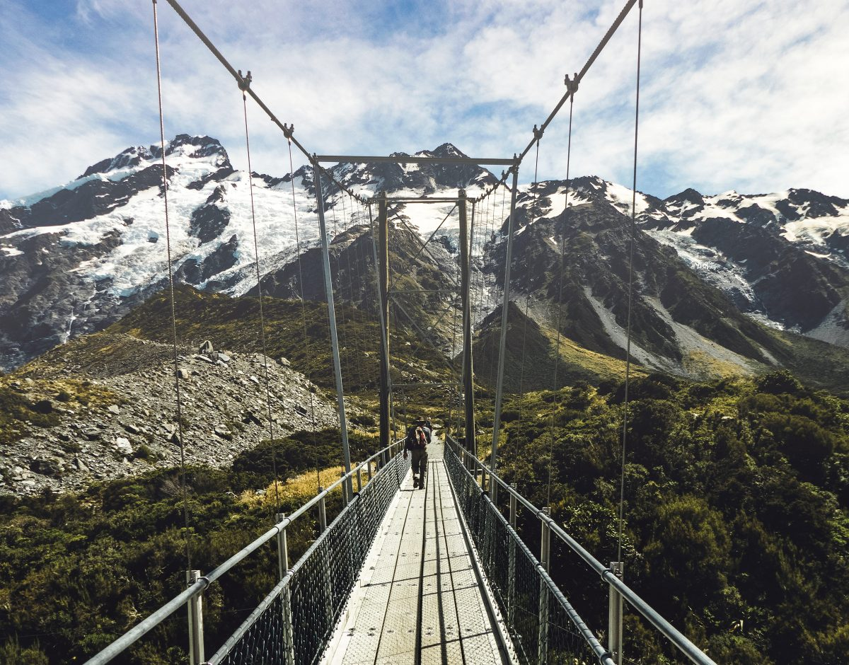 A hiker walks the suspension bridge as part of the Hooker Valley Track in Mount Cook National Park, New Zealand