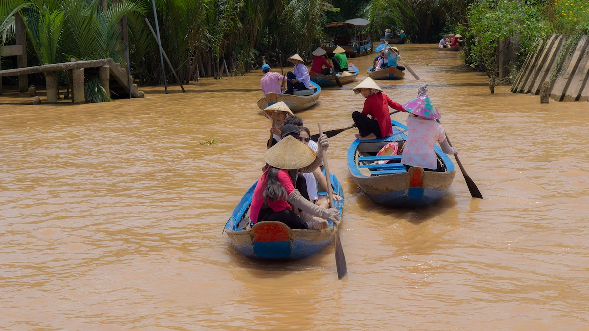 locals paddling boats on the Mekong Delta River in Cambodia