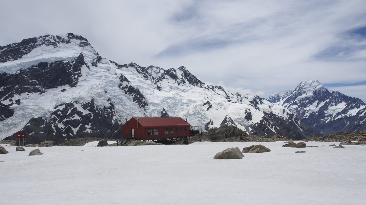 The distinctly red Mueller Hut sits in the middle of snow-covered ground as snow-capped mountains stand behind it