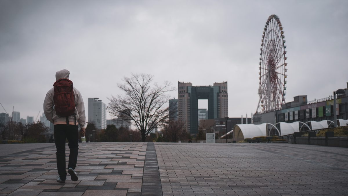 A man strolls through Odaiba as Palette Town's Ferris Wheel stands in the background