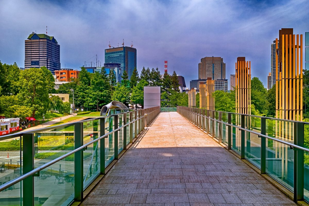 The view from a bridge in Roppongi shows a park against a cityscape