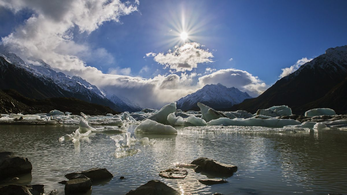 Icebergs broken from the Tasman Glacier float in the Tasman Lake seen from the Tasman Lake Viewpoint as the sun sits high above the mountains in Mount Cook National Park, New Zealand
