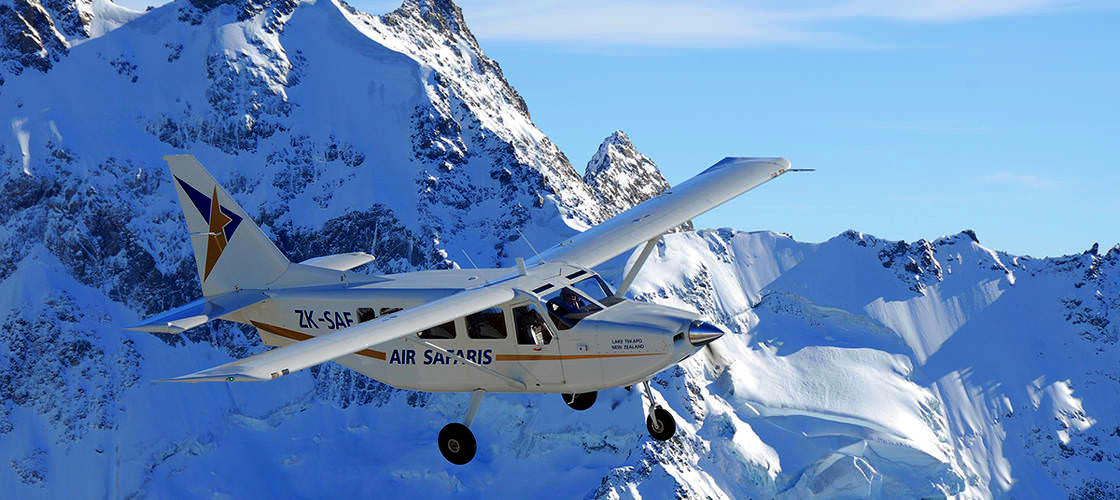 A plane from Experience Oz flies through the mountain range in Mount Cook National Park, New Zealand