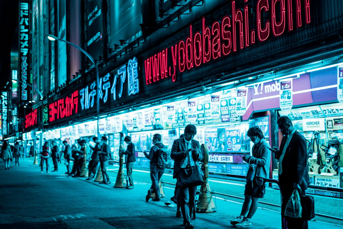 People staring at their phones stand outside the Yodobashi Camera store in Shinjuku, Tokyo, Japan