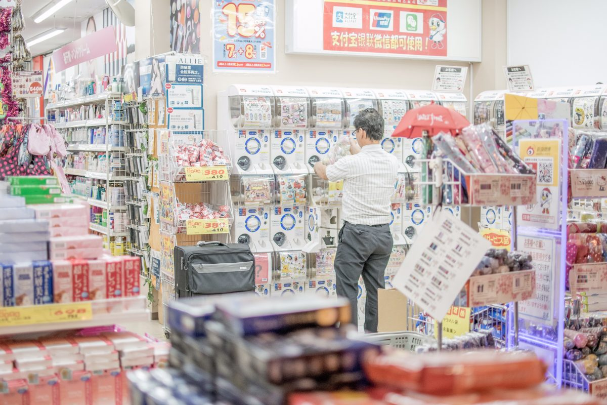 Photo of a man inside a well-lit Japanese store loading small knick-knack vending machines that are stacked on top of each other, with the rest of the store filled with various Japanese consumer goods and items in the foreground, left, right, and all around