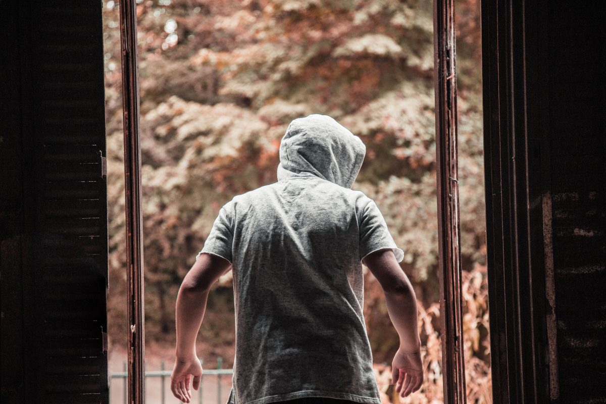 Photo of a man wearing a hooded grey shirt with his back turned towards the camera and him exiting from an entryway into sepia-colored woods