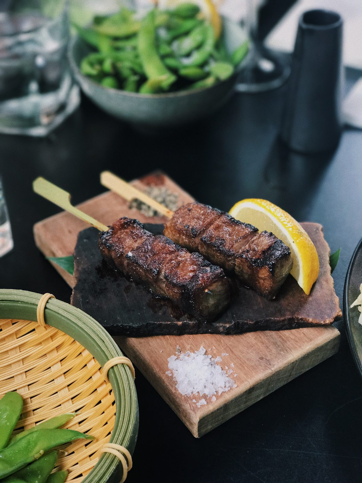 Photo of two sticks of beef chunks with three chunks per stick and a lemon slice on the side for decoration on a wooden block on top of a thicker wooden block on a black table with other bowls filled with greens on the sides with a cup of water blurred in the upper left background and a blurred dark grey container to the upper right