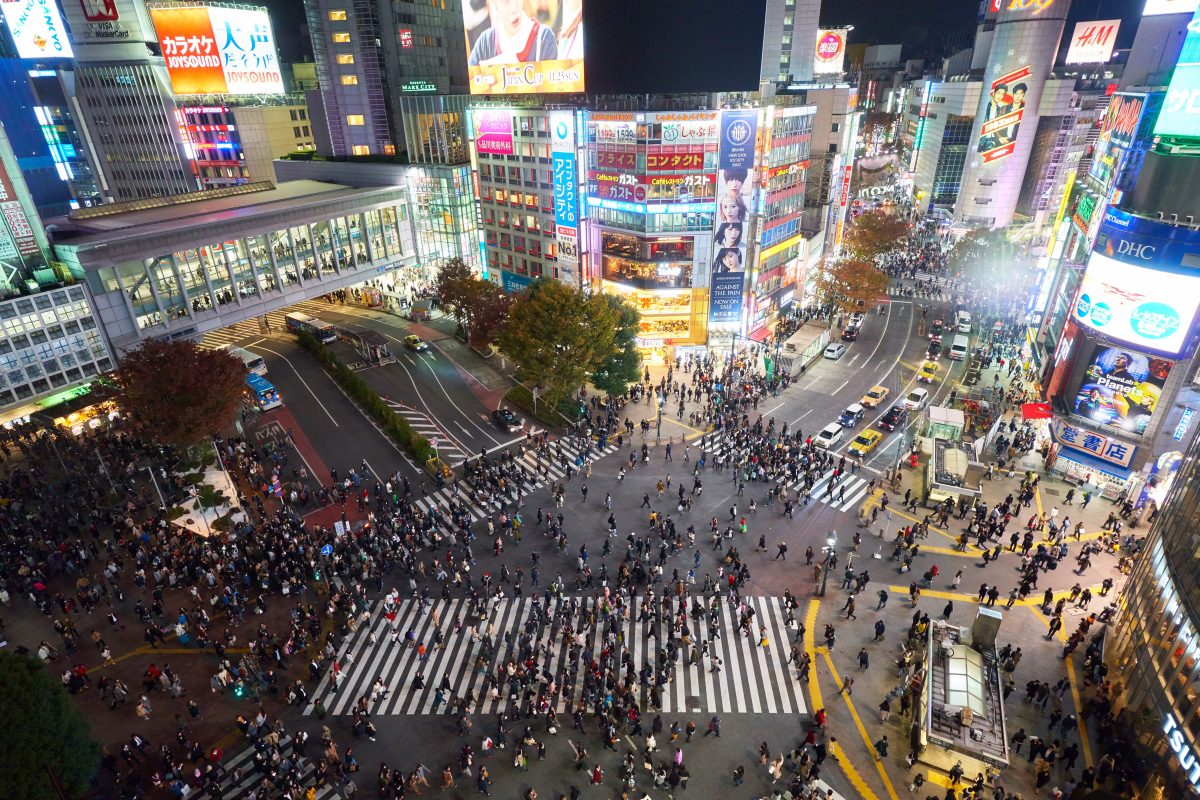 Bird's eye view of Shibuya Crossing at night with big crowds crossing the streets and surrounding areas as lights from the buildings and signages around the area illuminate the vicinity