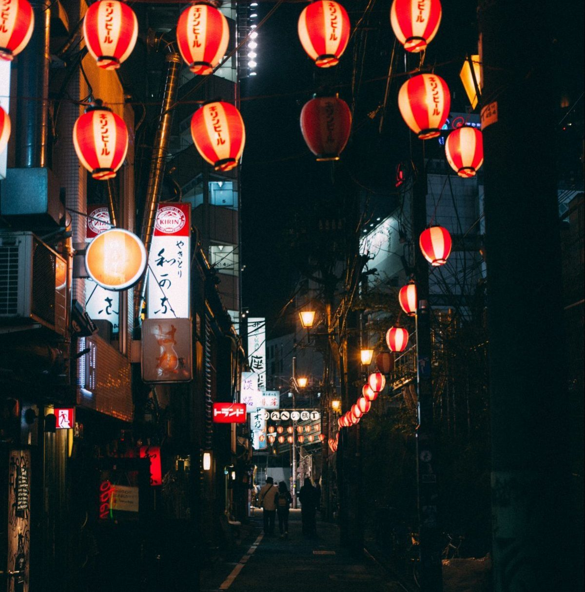 A dimly lit, small Japanese alleyway at night with red lanterns above lining the street and a few Japanese signages lit up with three people walking a few steps away