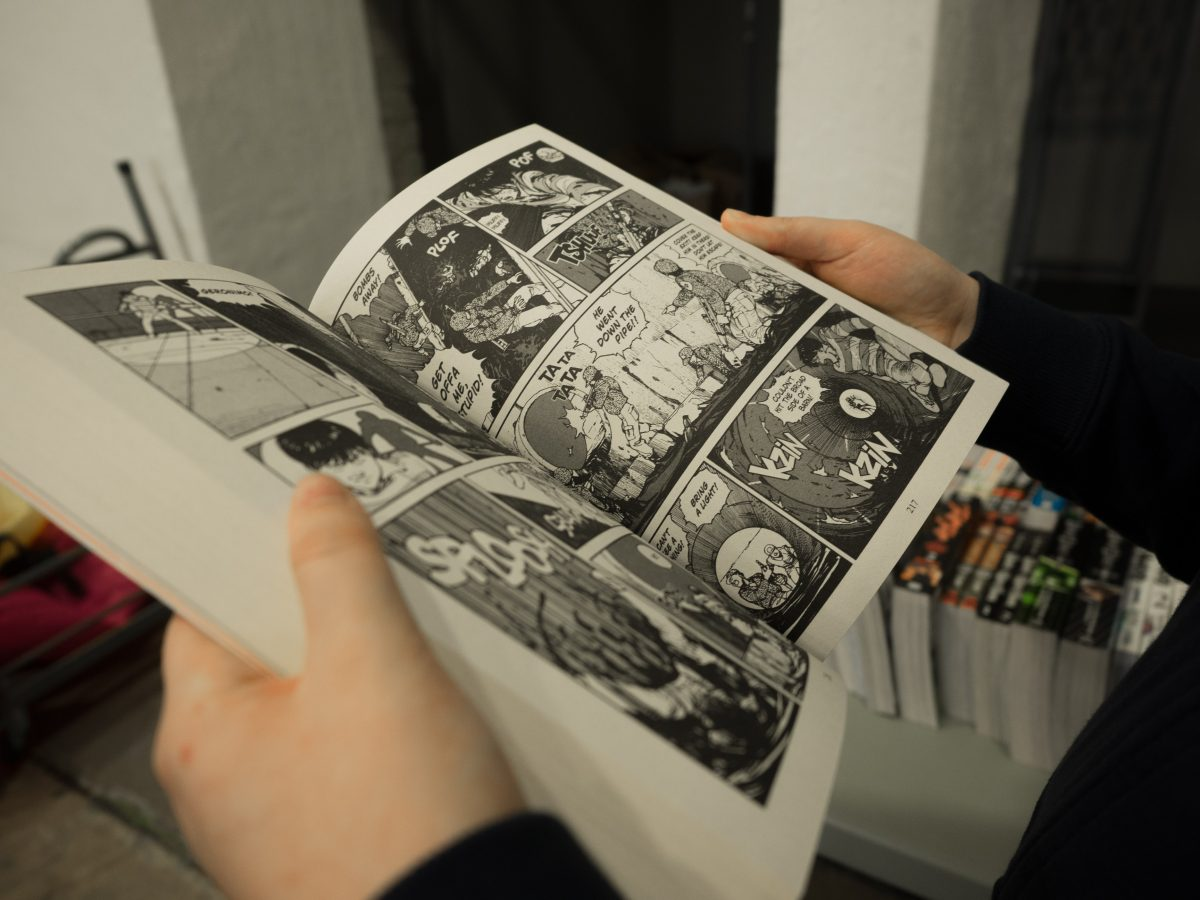 Closeup of hands holding open a manga that's black and white with other mangas in the background
