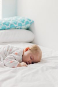 Photo of a baby with blonde hair sleeping on a bed, torso faced down, the bed has white sheets and white and blue pillows in the near distance, with the bed being against a white wall and the baby's wearing a long-sleeved white garment with orange polka dots