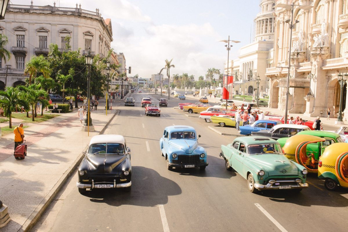 Photo of a wide road in Cuba with numerous colorful cars on the road that look retro with cream-colored Spanish style buildings on the blocks of the street with the city's buildings and palm trees in the background with an afternoon cloudy sky