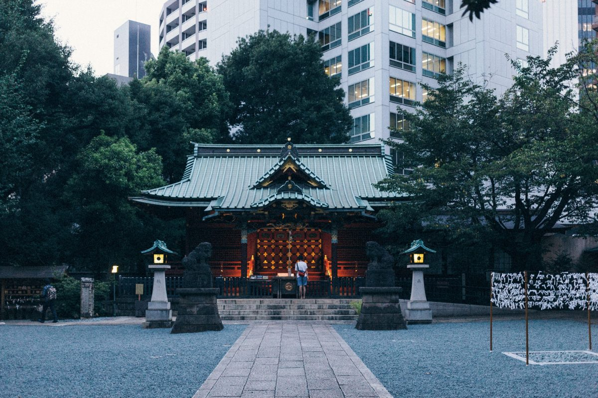 Photo of a Shinto shrine in Shibuya Tokyo with a dimly lit center and a person wearing a white shirt and blue shorts visiting, the shrine has a cemented path leading towards it and it is guarded by tow tiger statues and Japanese-style lights on both sides with trees surrounding the shrine and a backdrop of city buildings, the floor of the area is filled with pebbles and small rocks and to the right there is a structure of four thin wooden stands with string and lots of paper tied to the strings