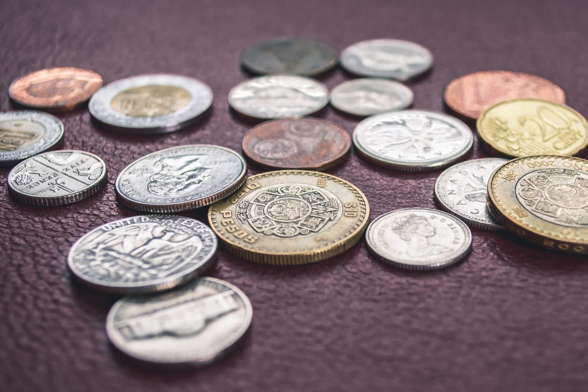 Photo of coins of different weights, colors, and currencies laid out on a brown leather surface