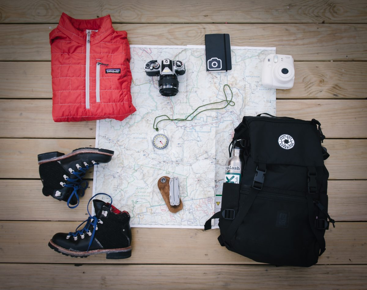 Camping essentials like the hiking shoe, bags, and hiking map