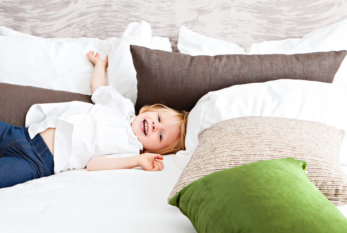 Photo of a blonde toddler wearing a white polo and blue jeggings while smiling while lying down on a white bed With large white, brown, and green pillows around the kid and a wave-patterned grey wall