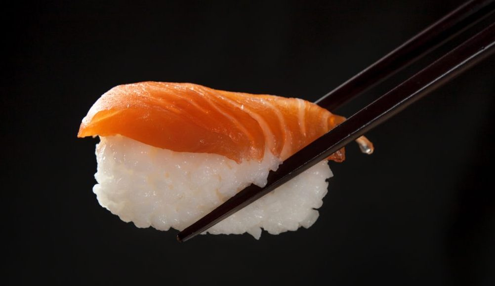 Salmon sushi being held by black chopsticks with a black background