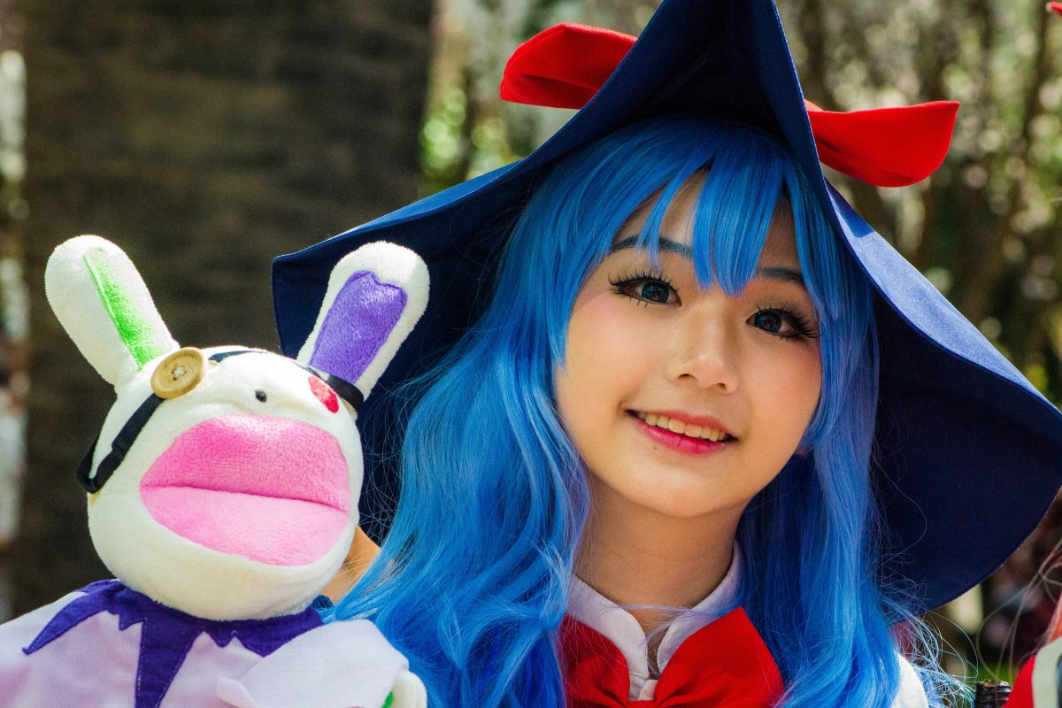 Photo of a girl with blue hair and makeup wearing a cosplay outfit with a big red ribbon below her neck and a big blue hat with a red ribbon while holding a white bunny with yellow and red buttons for eyes and big pink lips