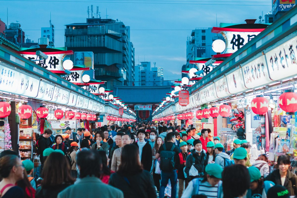 Photo of a busy night market with both left and right side lined with stalls next to each other with indistinct sign designs and red lanterns hanging from each stall, with Japanese style lights on top of the stalls and a busy crowd walking along the entire night market, with a view of buildings and a traditional style small Japanese structure at the end in the background