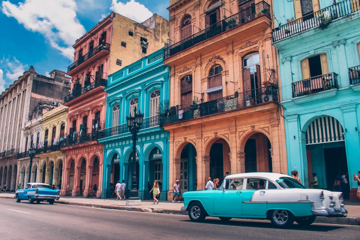 Photo of colorful Cuban buildings with orange, blue, and cream with archways in front of the buildings' entryways and balconies and blue retro style cars along the streets and people walking on the sidewalk, with the weather being bright and cloudy