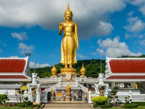 Golden standing Buddha at the peak at Hat Yai Municipality