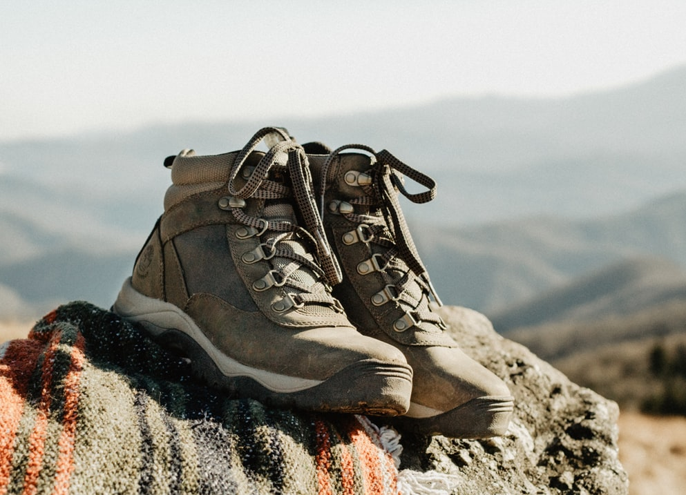 photo of a pair of hiking boots sitting atop a rock