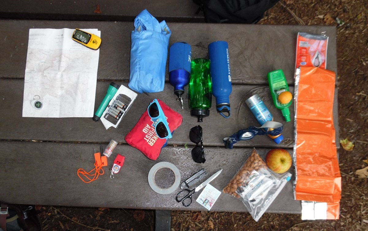 a photo showing all hiking essentials on a table