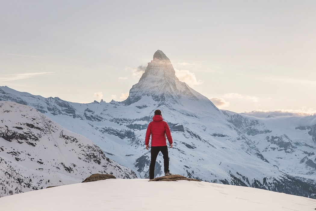 a man standing on top of a mountain looking at a mountain peak