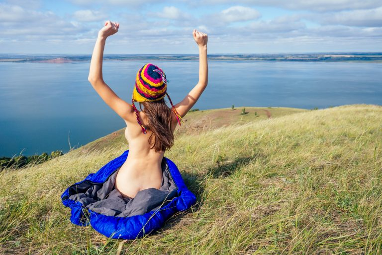 Back view of sexy naked woman tourist in a hat sitting in blue sleeping bag on the grass, enjoying sunny morning in the mountains lake after nude hiking.