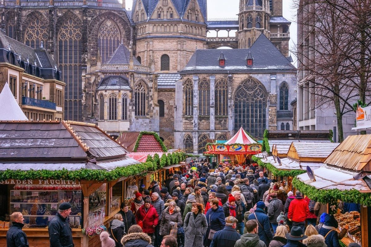 People walking through the Christmas market against the backdrop of the Aachen Cathedral in Aachen, Germany