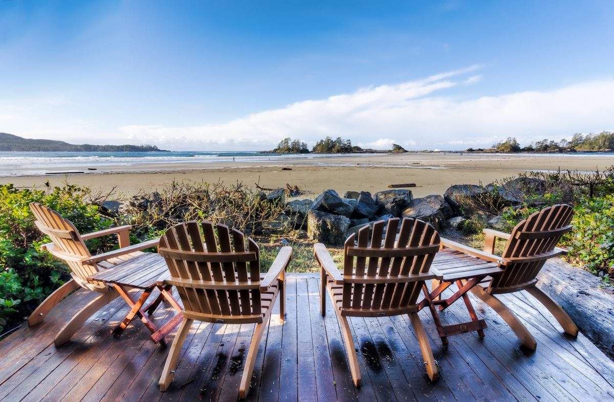 Unoccupied wooden chairs facing the sandy beach