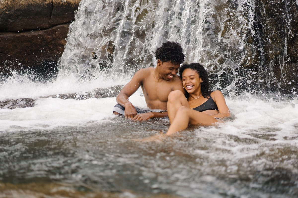 Two people enjoying the water from the falls