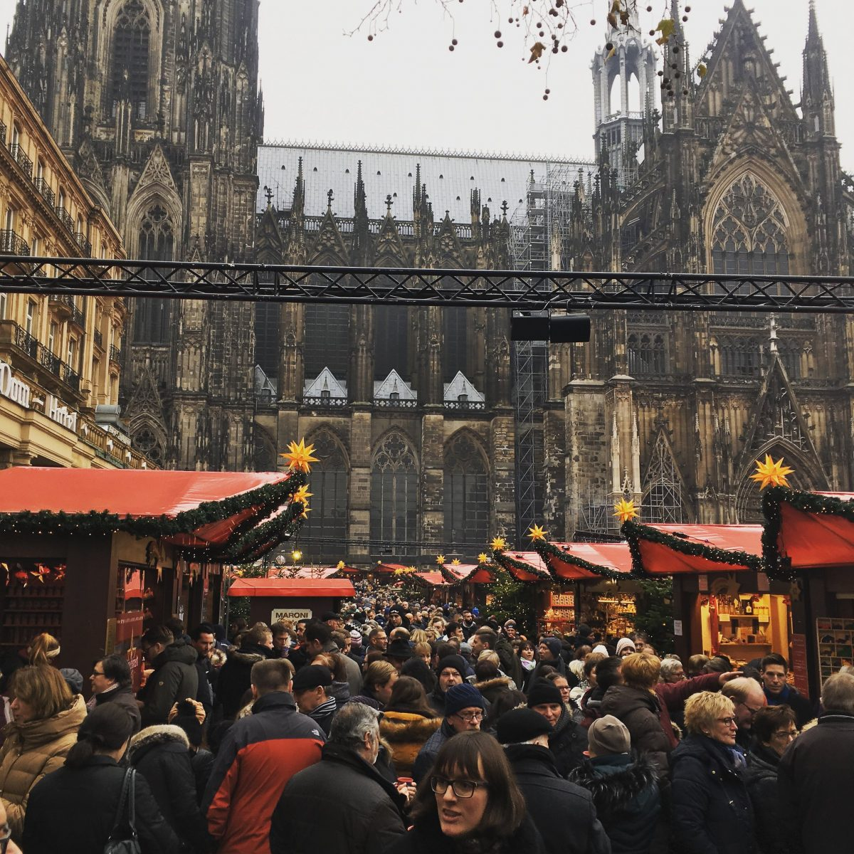A mass of people walking around the Cologne Christmas Market with Cologne Cathedral in the background in Cologne, Germany