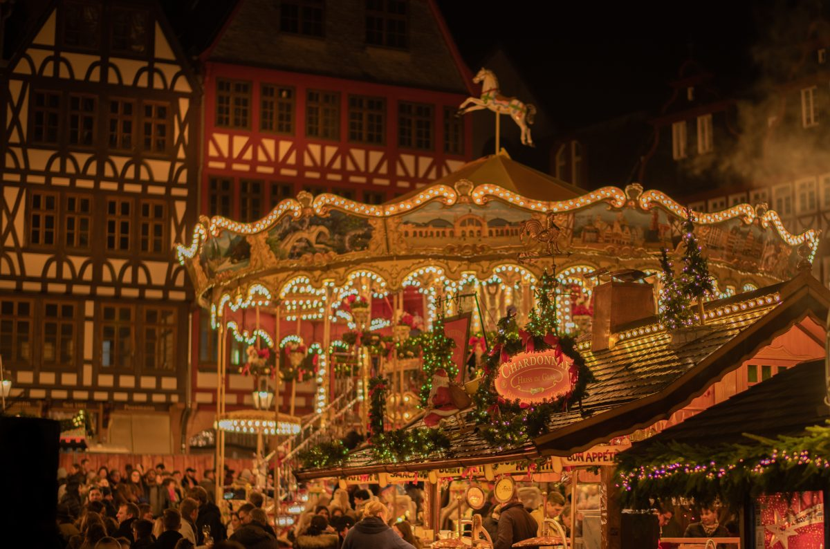 People walking around the Frankfurt Christmas market as a carousel spins in the background in Frankfurt am Main, Germany