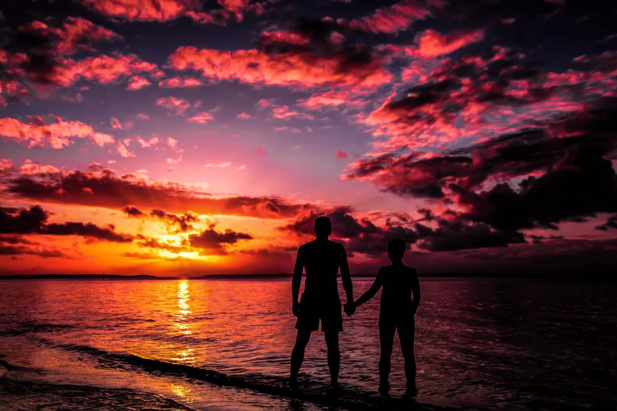 Silhouette of Couple while holding hands on a sunset background