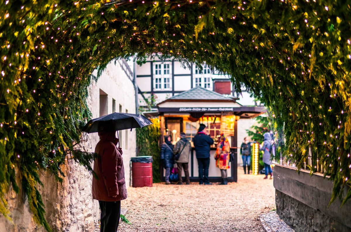A person stands with an umbrella under a decorated tunnel at the Goslar Christmas market in Goslar, Germany