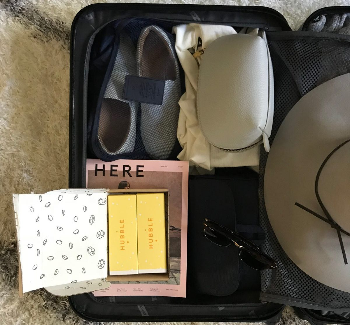 Black luggage packed with travel items
