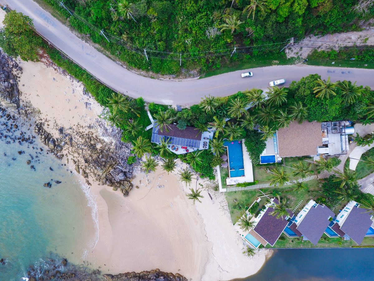 Aerial top view of a beach lined with resort accommodations in Koh Lanta