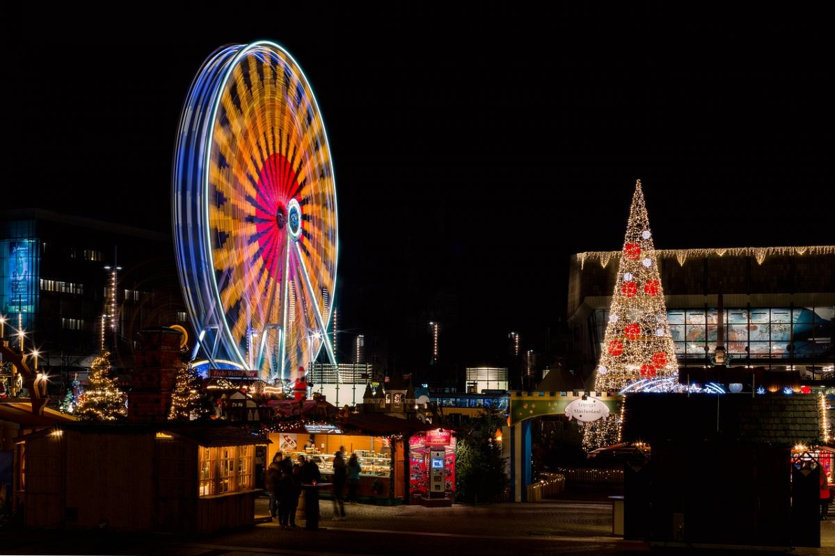 People walking around the Leipzig Christmas Market as a Christmas tree stands and a Ferris wheel spins in the background in Leipzig, Germany