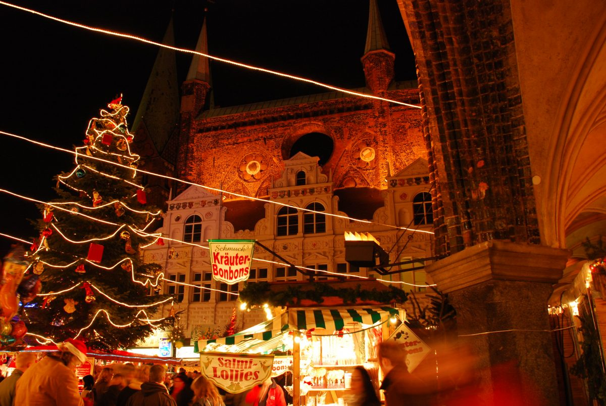People walking around the Lubeck Christmas Market decorated with a Christmas tree and hanging Christmas lights in Lubeck, Germany