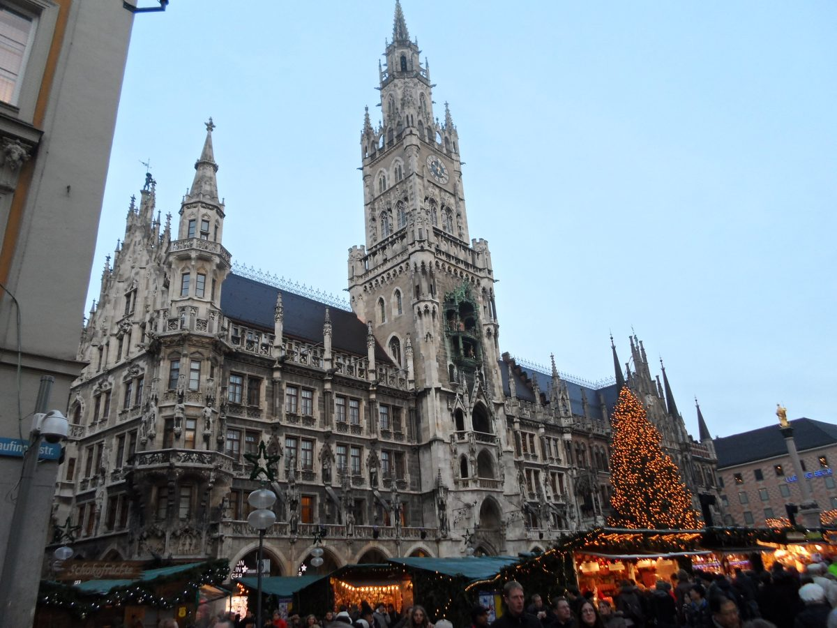 People walking around the Munich Christmas Market at the Marienplatz with the town hall standing in the background in in Munich, Germany