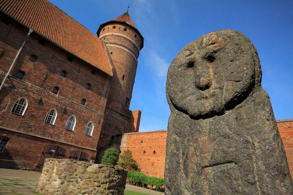 "The Prussian stone ""Baba"" stands outside the Gothic Olsztyn Castle in Olsztyn, Poland"